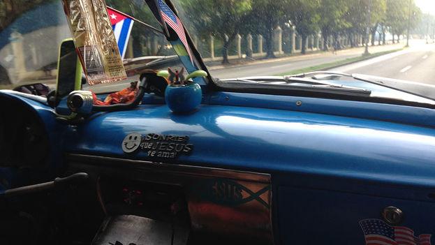 El signo de los tiempos: banderas cubana y estadounidense en un taxi de La Habana. (14ymedio)