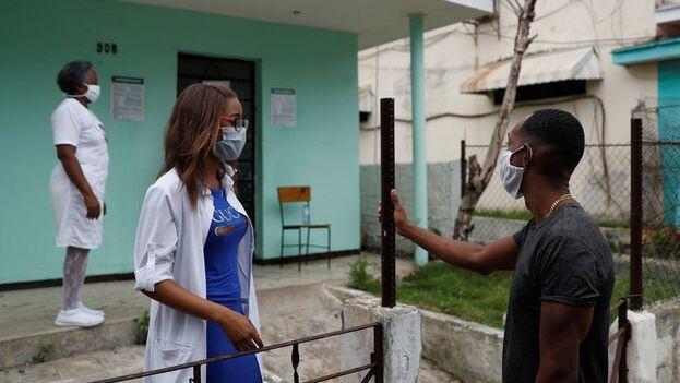 Un hombre conversa con una trabajadora de la salud en la entrada de un consultorio médico, en La Habana. (EFE/Yander Zamora/Archivo)