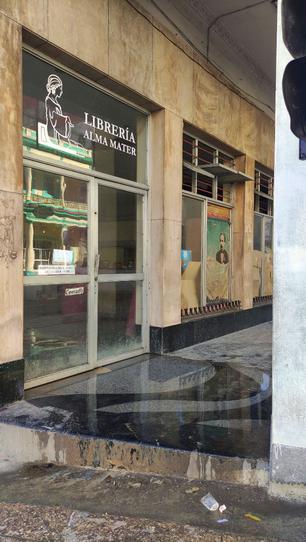 En las vidrieras de Alma Mater, sucias y cubiertas con pedazos de papel de estraza, se ve un desteñido afiche con el rostro de José Martí. (14ymedio)