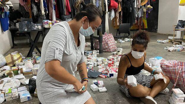 Una de las voluntarias abre paquetes, clasifica medicamentos, cuenta blísters, mientras la otra recibe mensajes, va formando pequeños paquetes en bolsas de plástico y atiende a los que van llegando. (14ymedio)