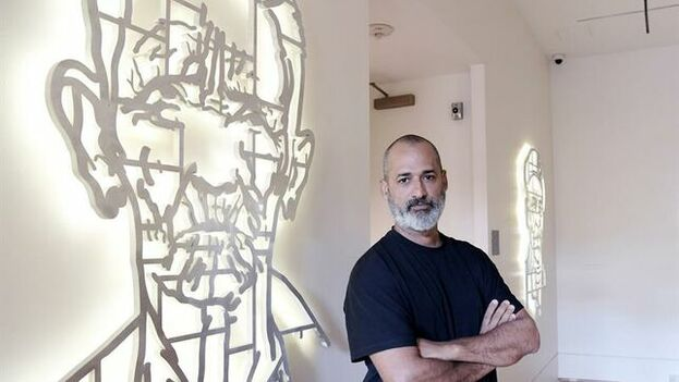 Marco Castillo, del colectivo Los Carpinteros, junto a su obra 'No es el Che, es Felicia', que forma parte de la exposición 'Cuba Va!' en el museo Phillips Collection de Washington. (EFE)