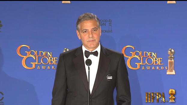 George Clooney, que luce la chapa en apoyo al semanario 'Charlie Hebdo', habla con la prensa tras la gala (Golden Globes/Youtube)