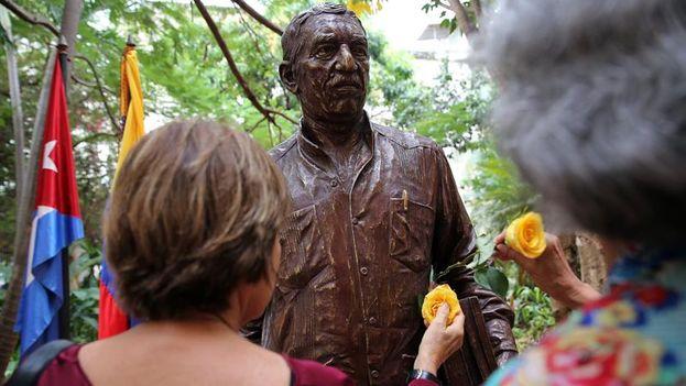 Personas dejan flores amarillas en la estatua del escritor colombiano Gabriel García Márquez, obra del artista cubano José Villa Soberón. (EFE/Alejandro Ernesto)