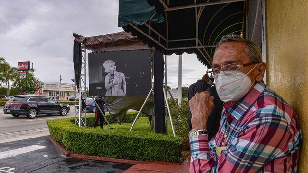 Un hombre espera mientras instalan un retrato de la cantante Rosita Fornés este viernes afuera de la Funeraria Auxiliadora Nacional en Miami. (EFE/Giorgio Viera)