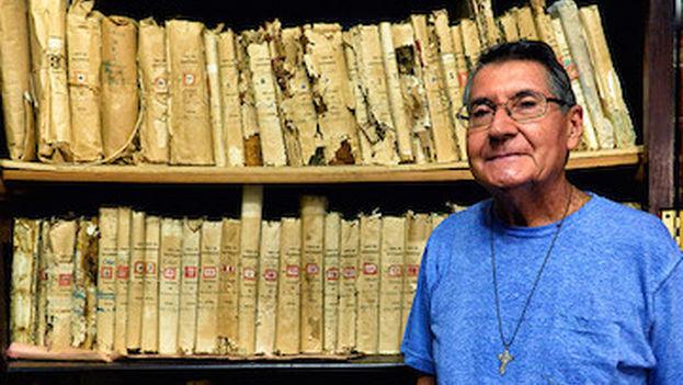 El padre Bendito, párroco de la iglesia de la Santísima Trinidad, junto a parte de los archivos y fotografiado por David Lafevor. (D.L./Vanderbilt University)