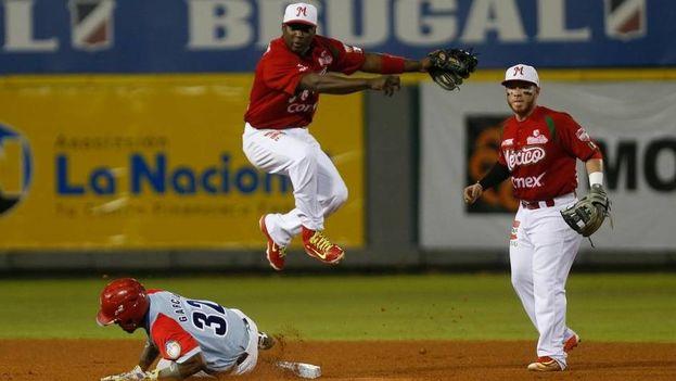 José Adolis García, de Ciego de Avila,intenta alcanzar la base pero Yuniesky Betancourt, de los Venados de Mazatlán, lo pone out en el estadio de Quisqueya, en Santo Domingo, el sábado 6 de febrero del 2016. (Orlando Barría/EFE)