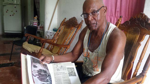 Orlando Ortega abuelo mostrando un álbum de recortes de su nieto. (14ymedio)
