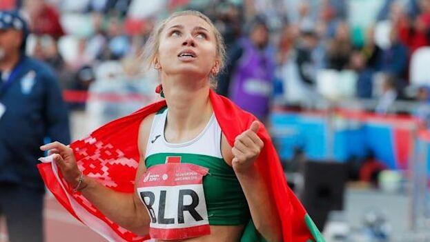 La atleta bielorrusa Krystsina Tsimanouskaya envuelta en la bandera de su país durante una competición. (EFE)