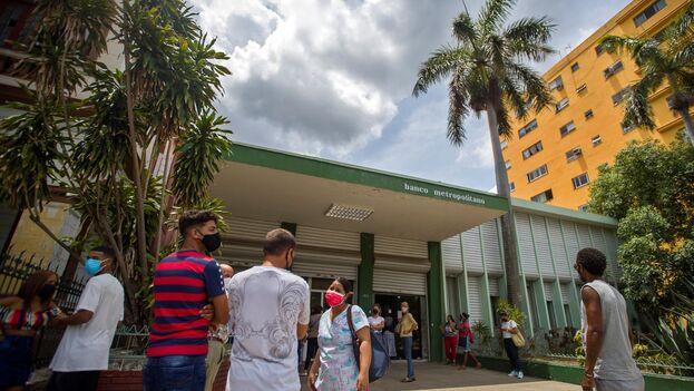 Varias personas esperan su turno para entrar a un banco en La Habana. (Yander Zamora/EFE)