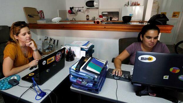 Dos trabajadoras de Mandao, el nuevo servicio de mensajería y comida a domicilio inspirado en Uber Eats y Glovo, en La Habana. (EFE/Ernesto Mastrascusa)