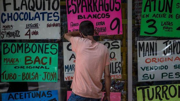 Un hombre camina frente a una vitrina de la que cuelgan carteles con precios de alimentos en Caracas, Venezuela. (EFE/Miguel Gutiérrez/Archivo)