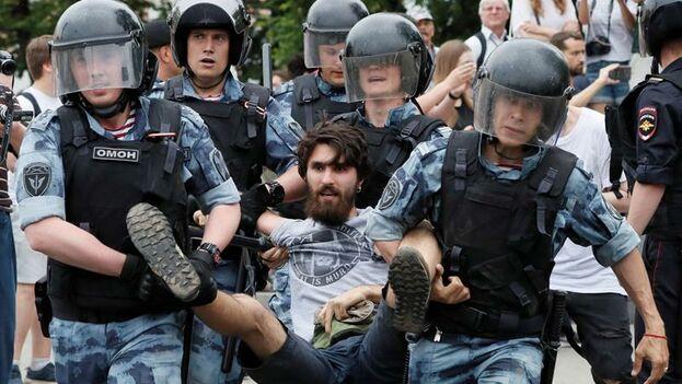 Agentes de la Guardia Nacional rusa detienen a varios participantes durante la manifestación. (EFE/ Yuri Kochetkov)