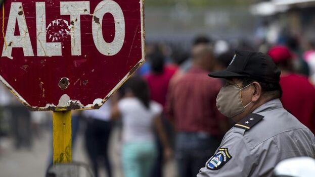 Agentes en La Modelo forman un cordón de seguridad tras el anuncio de excarcelación de presos y la aglomeración de familiares que los esperan este miércoles, en la ciudad de Tipitapa. (EFE)