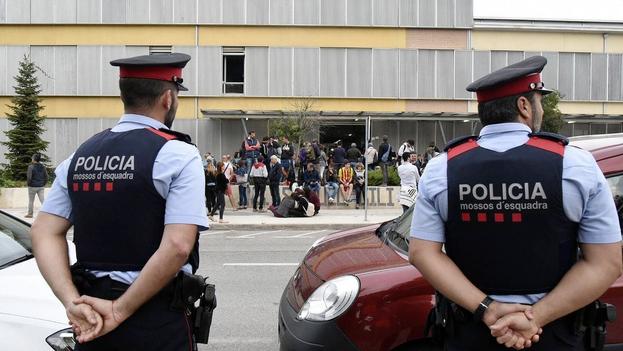 Agentes de la Policía Nacional y la Guardia Civil se han desplegado por los colegios electorales de Cataluña para impedir el referéndum ante la pasividad de los Mossos d'Esquadra. (EFE)