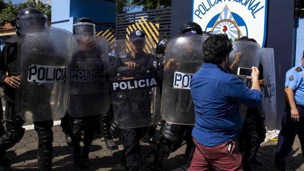 Agentes de la policía nacional repliegan al periodista Wilfedo Miranda del semanario 'Confidencial' al llegar a la sede central de la policía a pedir explicaciones sobre el allanamiento del medio de comunicación. (EFE/Jorge Torre)