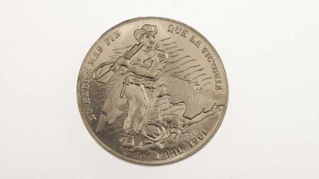 Anverso de la moneda, con el mapa de Cuba y un rebelde sobre un revolucionario caído. (Twitter/@CIA)