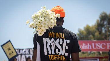 Un manifestante sostiene un ramo de flores en una manifestación organizada bajo el lema Black Lives Matter. (EFE/EPA/Christian Monterrosa)