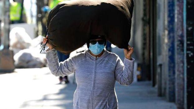 Una mujer con una mascarilla por el coronavirus, en El Bronx, Nueva York. (Peter Foley/ EFE)