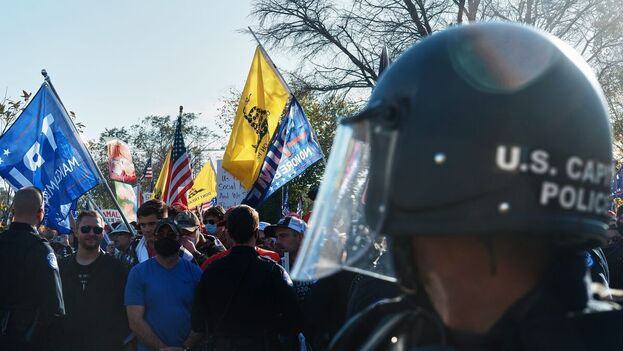 Un agente de policía del Capitolio de los EE UU vigila a los partidarios de Trump, reunidos frente a la Corte Suprema, en Washington. (EFE)