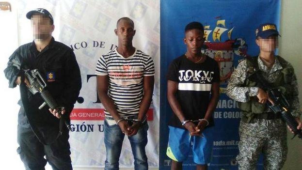 En el centro, esposados, los presuntos asesinos de la pareja de cubanos, Carlos E. Ibargüen (i) y Johan E. Carreazo (d). (Policía colombiana)