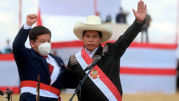El presidente peruano, Pedro Castillo, a la derecha, celebra con Guido Bellido luego de elegirlo como primer ministro de su Gobierno, durante una ceremonia simbólica de juramentación, este jueves en la Pampa de la Quinua, en Ayucucho (Perú). (EFE/Presidencia Perú)