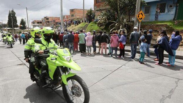 Centenares de personas hacen fila para inscribirse a las ayudas alimentarias del Gobierno durante la cuarentena por el covid-19. (EFE)