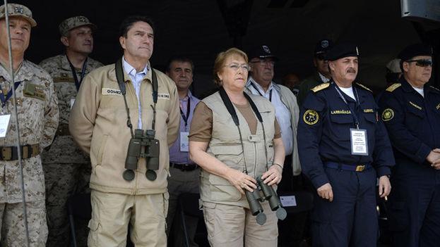 La presidente de Chile, Michelle Bachelet acompaña del ministro de defensa en un entrenamiento militar. (EFE)