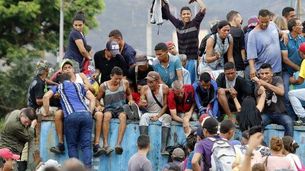 Cientos de personas cruzan el Puente Internacional Simón Bolívar a pesar de los contenedores que lo bloquean, este martes, en Cúcuta. (EFE/ Schneyder Mendoza)
