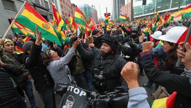 Ciudadanos bolivianos y policías festejan la renuncia del presidente de Bolivia, Evo Morales, este domingo en La Paz. (Martín Alipaz)
