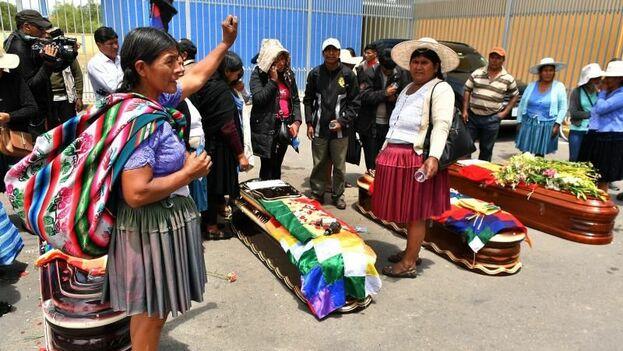 Ciudadanos rodean los féretros de varios de los fallecidos tras los disturbios con las fuerzas del orden, frente al Instituto de Investigaciones Forenses este sábado, en Cochabamba. (EFE)