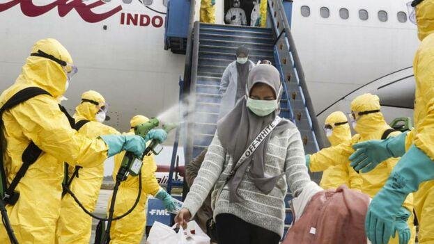 Ciudadanos indonesios evacuados de Wuhan, China, son rociados con antiséptico a su llegada al aeropuerto Hang Nadim en Batam. (EFE)