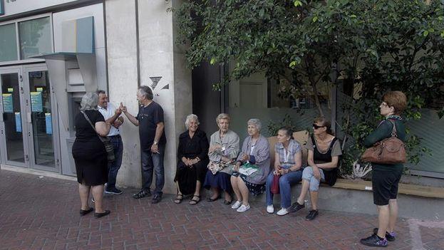 Ciudadanos griegos ante una sucursal de banco el primer día de medidas de control de capitales que se mantendrán al menos hasta el domingo 5 de julio. (EFE/ORESTIS PANAGIOTOU)