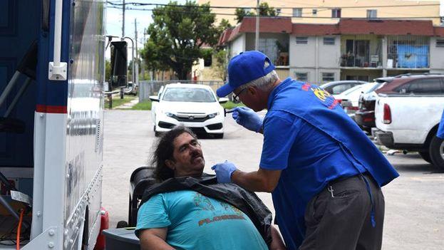 Un hombre afeita a otro a las afueras del edificio Civic Tower de Allapattah. (EFE/Jorge I. Pérez)