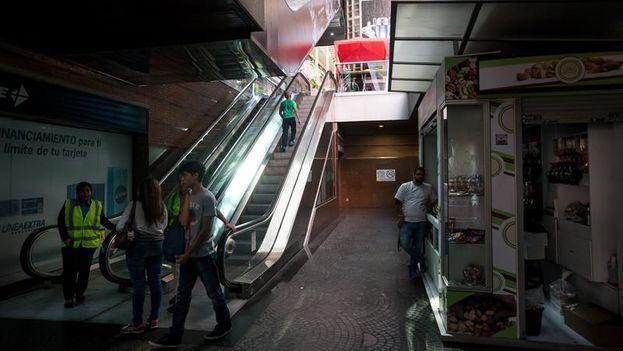 Clientes de un centro comercial en Caracas suben por las escaleras eléctricas, apagadas por el racionamiento. (Miguel Gutiérrez/EFE)