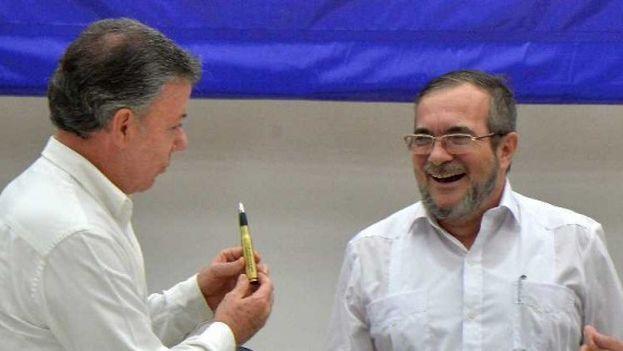 El presidente de Colombia, Juan Manuel Santos le ofrece un balígrafo a Timochenko para firmar la paz. (EFE)