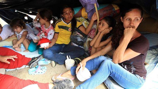 Colombianos retornados voluntariamente desde Venezuela permanecen con sus pocas pertenencias bajo un plástico en La Parada (Colombia). (EFE/Mauricio Dueñas)