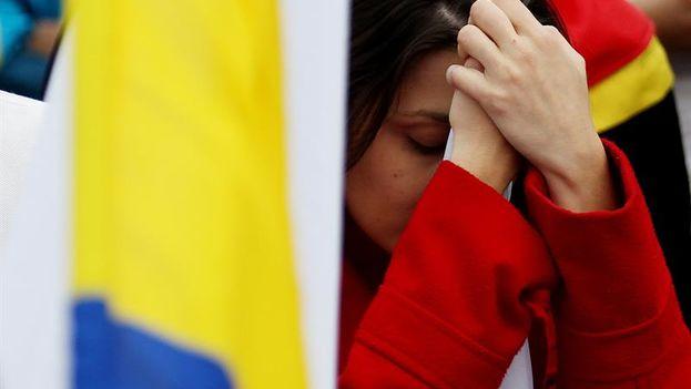 Colombianos reaccionan tras escuchar los resultados del plebiscito este domingo, en Bogotá. (EFE/L. Muñoz)
