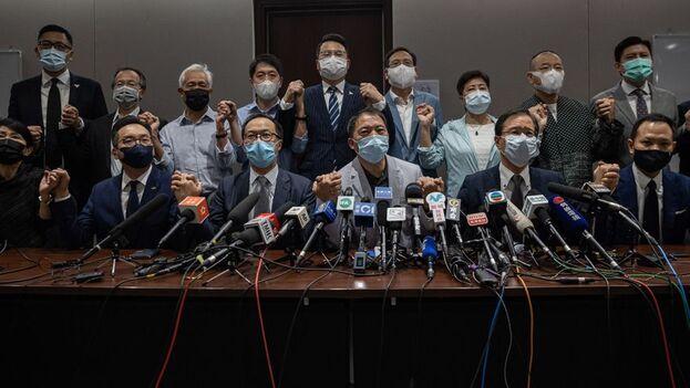 Los 19 diputados opositores en el Consejo Legislativo ofrecen una rueda de prensa para anunciar su dimisión en masa después de que cuatro de ellos fuesen destituidos de sus escaños, este miércoles en Hong Kong. (EFE/Jérôme Favre)