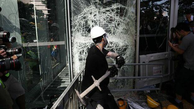Un manifestante rompe una cristalera del Consejo Legislativo en Hong Kong (China) este lunes. (Ritchie B. Tongo / EFE)