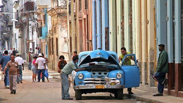 """Cubanos intentan reparar un """"almendrón"""" en La Habana. (SN)"""