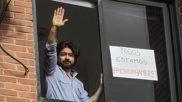 Daniel Ceballos, saluda desde la ventana de su casa donde cumplía arresto domiciliario. (EFE)