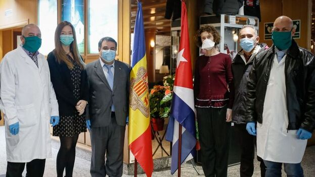 Dariel Romero, el médico que supuestamente ha abandonado la misión, penúltimo empezando por la izquierda, junto a la ministra de Sanidad María Ubach. El cónsul en Barclona, Alain González, junto a la bandera andorrana. (Altaveu)