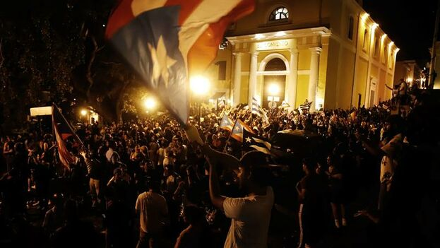 Decenas de personas celebran tras el anuncio del gobernador de Puerto Rico, Ricardo Rosselló, este miércoles, en los alrededores de la Fortaleza, en San Juan. (EFE/ Thais Llorca)