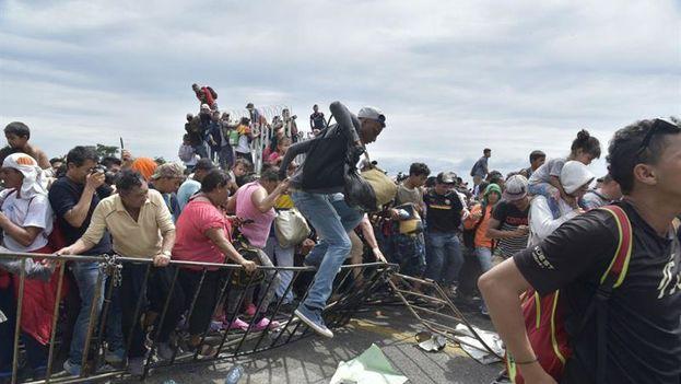 Después de momentos de tensión, por el sofocante calor y el hacinamiento, la multitud sobrepasó el cordón policial y cruzó la frontera ante la mirada pasiva de los agentes. (EFE)