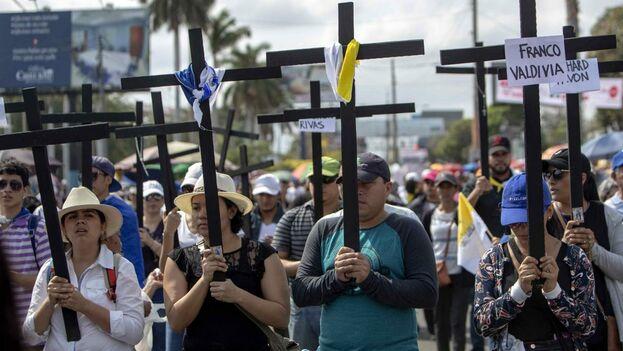 """Docenas de manifestantes gritaban """"justicia"""" y cargaban cruces de madera con los nombres de quienes fallecieron durante las movilizaciones del año pasado. (EFE)"""