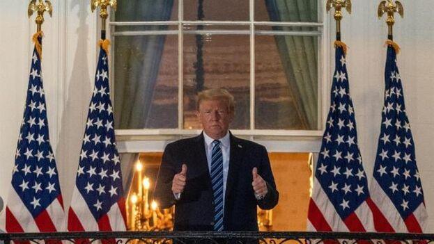 El presidente de EE UU, Donald Trump, saluda desde un balcón de la Casa Blanca después de salir del hospital donde estuvo tres días ingresado por covid. (EFE/Ken Cedeno)