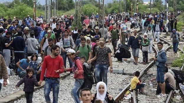 Emigrantes caminan por las vías del tren, en la ciudad de Gevgelija, Macedonia (Foto EFE)