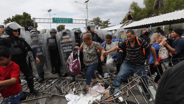Emigrantes hondureños cruzan el perímetro de seguridad establecido por la Policía mexicana y entran a ese país en busca de continuar su camino a la frontera de Estados Unidos. (EFE)