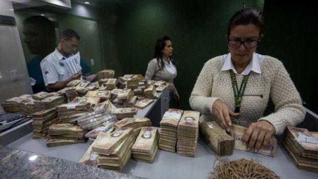 Empleados de banca trabajan en la retirada de los billetes de 100 bolívares. (EFE)