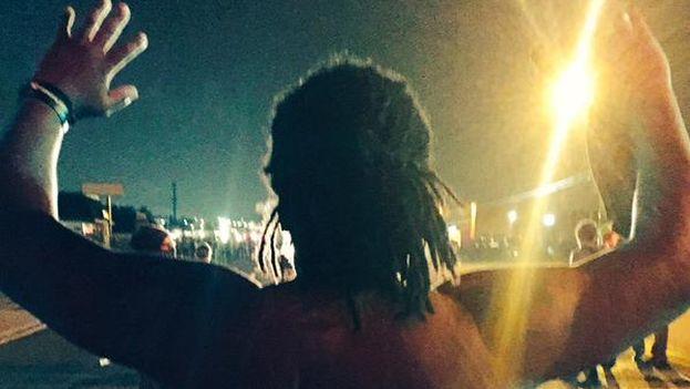 Un joven levanta los brazos delante de la policía en Ferguson durante la conmemoración de la muerte de Michael Brown. (@MichaelSkolnik)